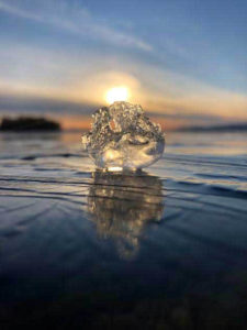A chunk of ice with sunset behind it