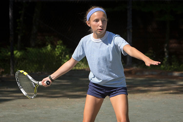 A Wohelo camper playing tennis