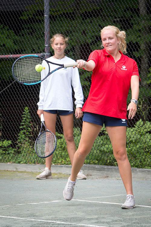 A counselor teaching tennis skills