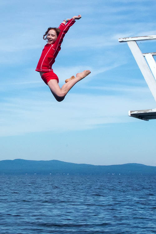 A Wohelo Camper jumping off the diving board